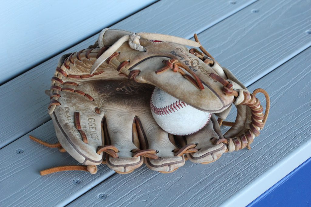 An image of a dirty, used and dry baseball glove holding a baseball.  How would you dye this glove?