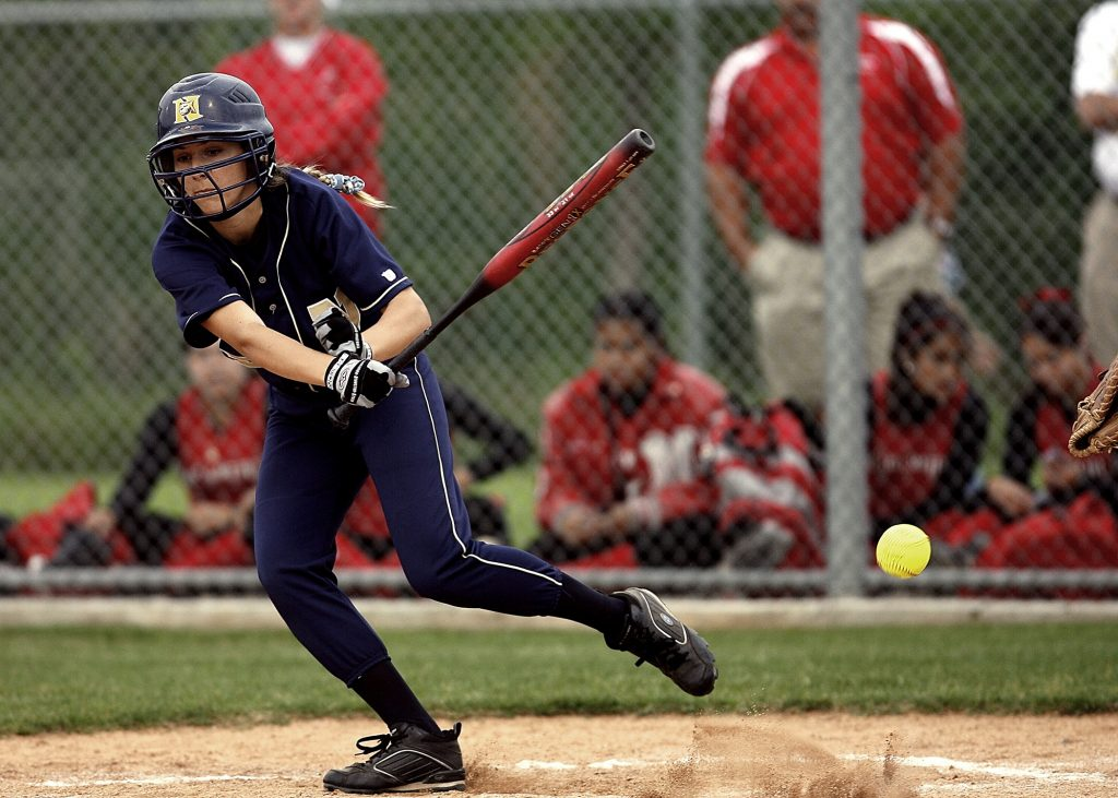 A girl starting to run after she finished her hit. She is still holding her bat.