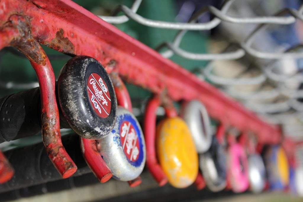 Lots of bats in a rack at a fence. Maybe some of them are the best baseball bats 2020?