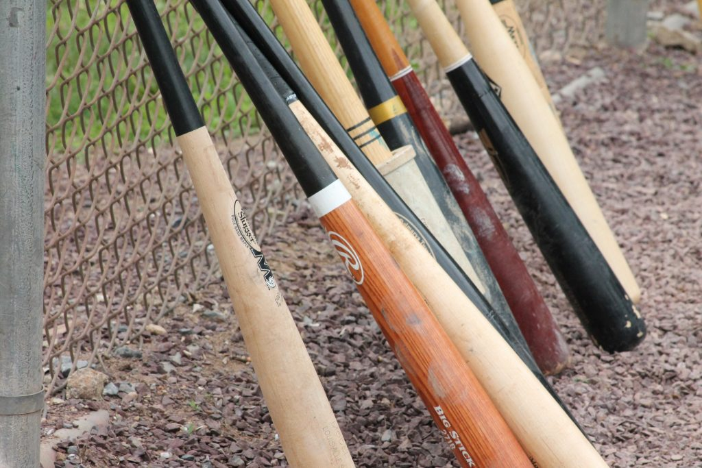 A lot of wood bats standing at a fence. Maybe these are the best baseball bats 2020.
