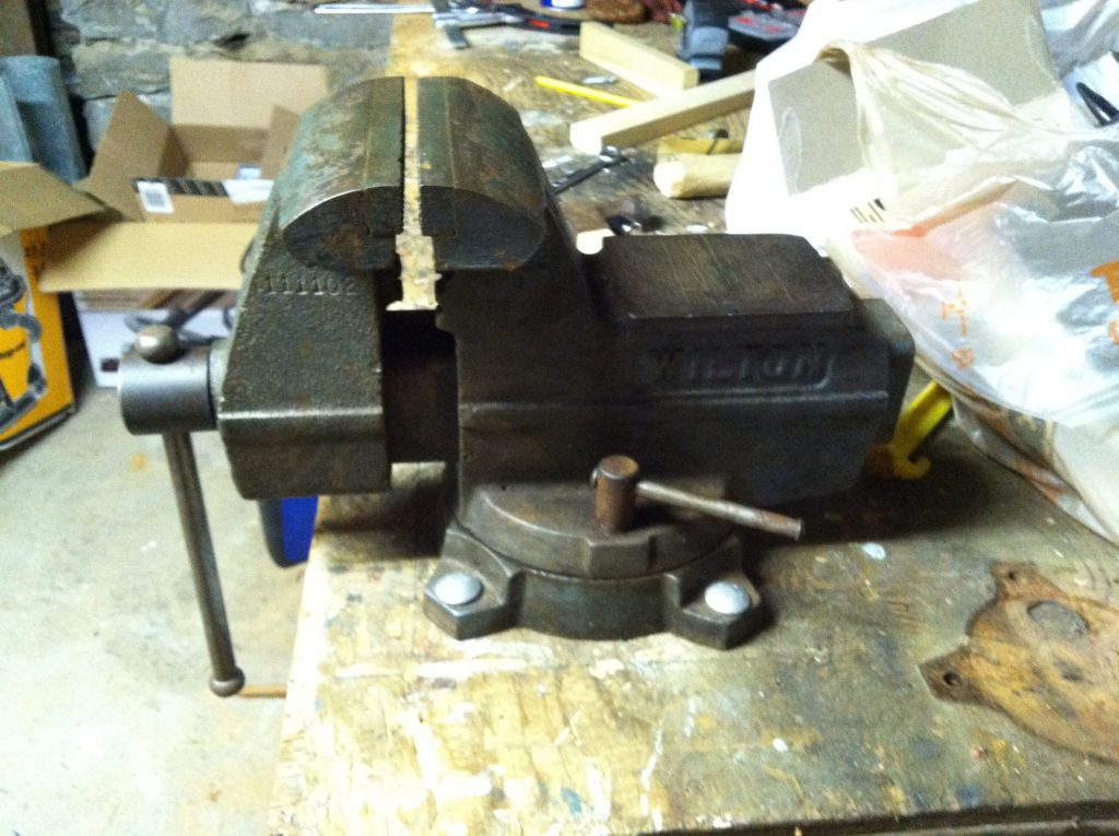 A closed vise on a table with nothing in it. This tool is great for bat juicing.